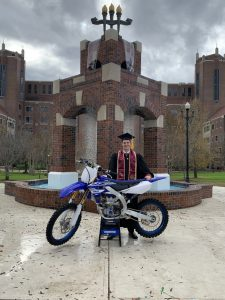 Josh Cartwright with his motor bike on graduation day
