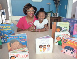 Maya's Book Nook Owner Lakeisha Johnson and her daughter Maya Johnson, 5, pose together with a collection of books in their home.
