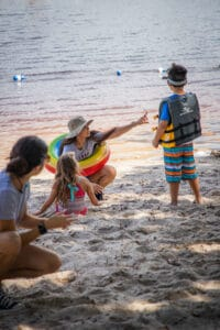 Counselors playing with campers on the beach.