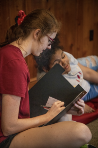 Camp counselor reading to camper.